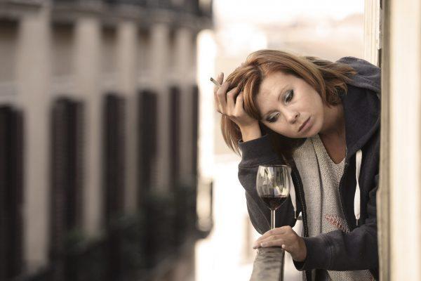 Привлекателна млада жена страдаща от депресия, пуши и пие вино на балкона