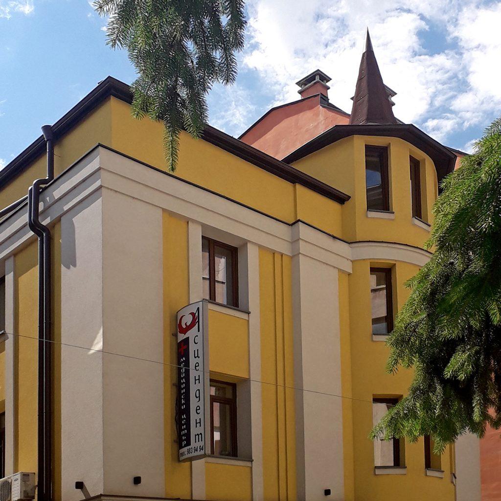 Сграда с жълта фасада и островърха кула
